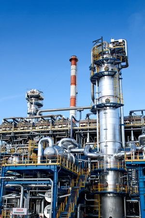 Oil industry equipment installation, metal industrial skyline over blue sky