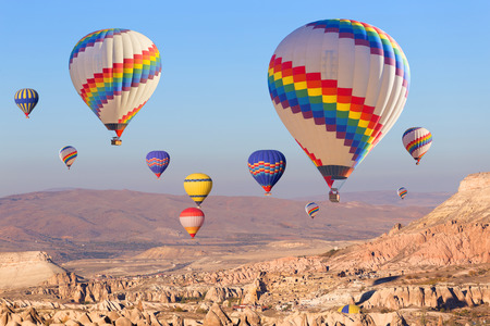 aeronautical: Balloons flying over rock landscape at Cappadocia Turkey.
