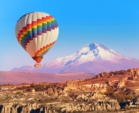goreme: Balloon flying over rock landscape at Cappadocia Turkey with Erciyes Mountain.
