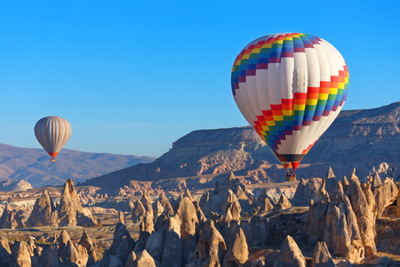 Balloons flying over rock landscape at Cappadocia Turkey.