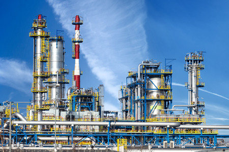 Petrochemical plant, oil refinery factory over blue sky. Imagens