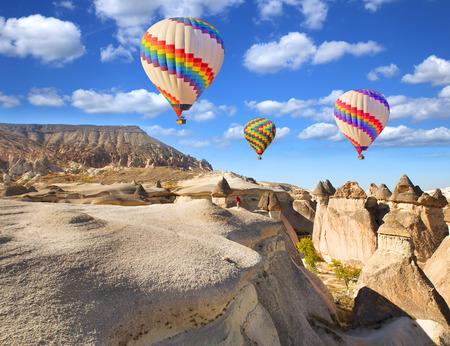 카파도키아 터키에서 바위 풍경을 통해 뜨거운 공기 풍선 비행. 스톡 콘텐츠
