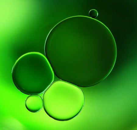 the surface of the water: Abstract background, green oil droplets on water surface. Beautiful macro abstraction Stock Photo