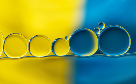 Abstract background with oil drops on water, yellow and blue macro. Banque d'images