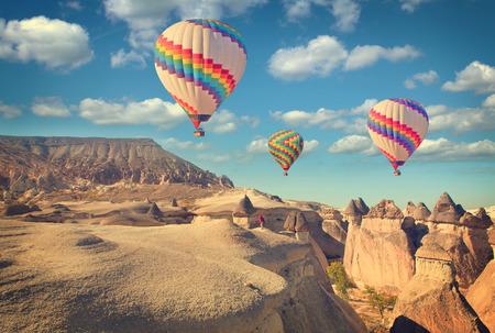 Foto d'epoca della mongolfiera che vola sopra il paesaggio di roccia a Cappadocia in Turchia. Archivio Fotografico - 44519607