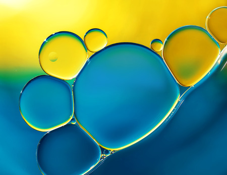 macros: Abstract background with oil drops on water, yellow and blue macro. Stock Photo