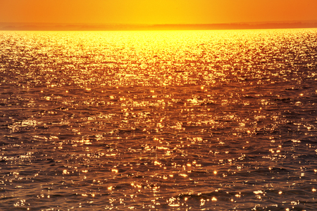 Glittering water at sunset. Sea water background.