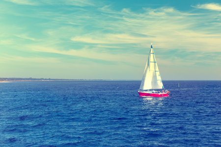 spinnaker: Seascape with sailboat the background of the blue sky and ocean.