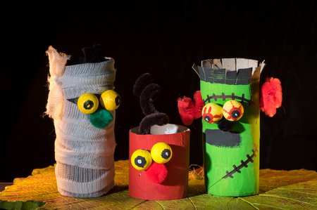 Closeup of a childs handicraft figurines made of toilet paper rolls and a clay pumpkin Stock fotó