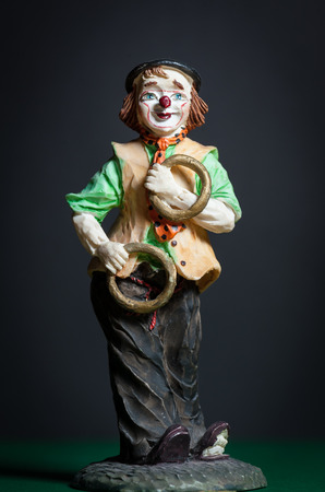 Closeup of a small figurine of a juggling clown with rings