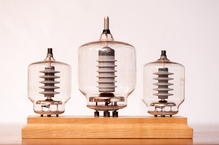 Three old vacuum transmitting tubes in front of a white background Stock Photo