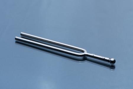 Close-up van een stemvork die op een weerspiegelende ondergrondse ligt Stockfoto