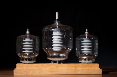 Three old vacuum transmitting tubes in front of a black background