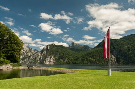 Austrian flag on a sunny day in Traunkirchen with Traunstein in the background