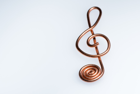 Closeup of a treble clef made of bent copper wire