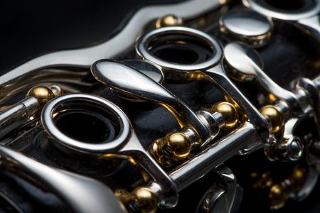 Details van een klarinet met zilveren sleutels en gouden contactdozen op zwarte achtergrond Stockfoto