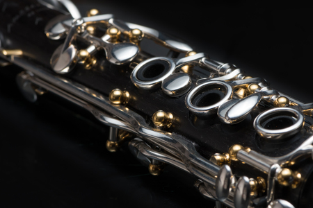 Details of a clarinet with silver keys and golden sockets on black background