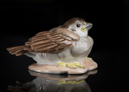 Closeup of a small porcelain sparrow standing on a black reflective surface