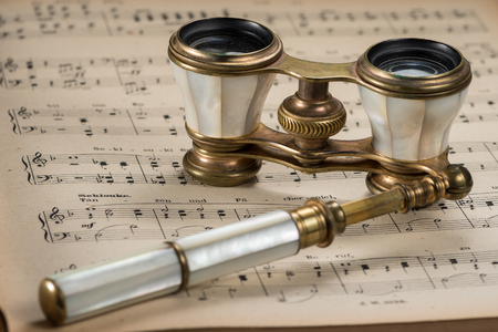 Closeup of old antique opera glasses lying on musical scores Foto de archivo