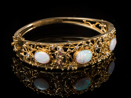 Closeup of a golden bangle with three opal gemstones Stock Photo