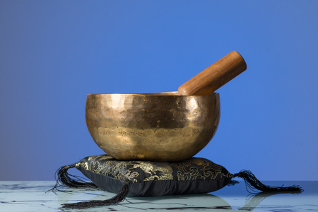 A small tibetan singing bowl in front of blue background, cushion and wooden striker