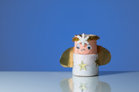 A childs handicraft angel with a candle, blue background