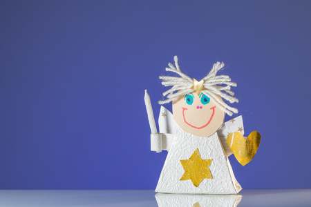 A child's handicraft angel with a candle, blue background