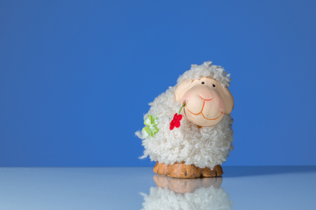 Figurine of a funny white sheep with a red flower, blue background Stock Photo