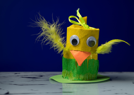 Closeup of a small yellow chick made of toilet paper roll by a child