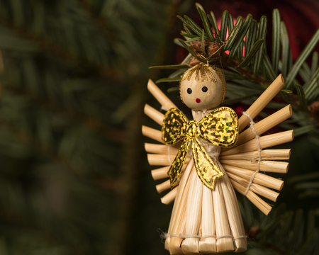 Closeup of an angel made of straw hanging on a christmas tree