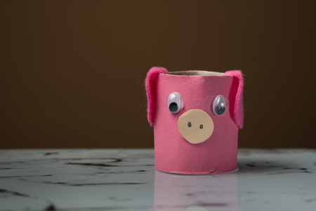 Closeup of a small pig made of toilet paper roll by a child