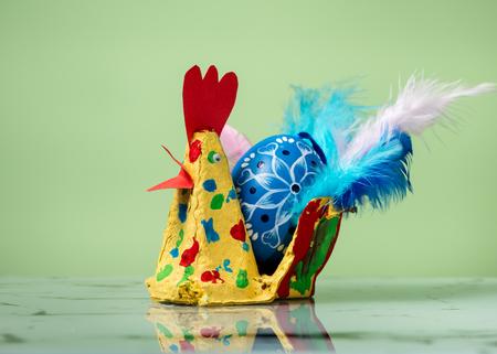 Closeup of a colorful handicraft chicken with a blue easter egg, light green background Standard-Bild