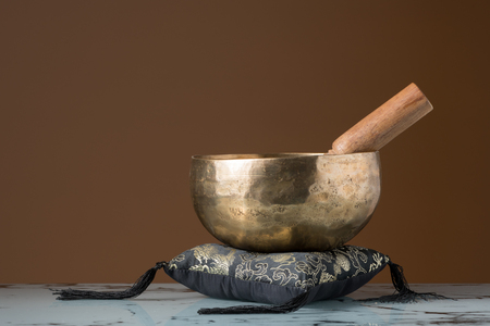 A singing bowl standing on a black cushion, brown background