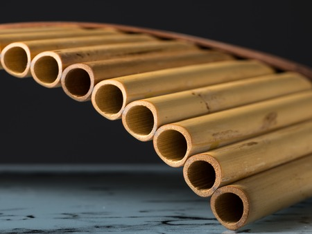 Detailed closeup view of a pan flute, dark background