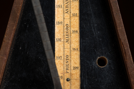 Detail of an old mechanic musical metronome, scale showing the various tempos Stock Photo