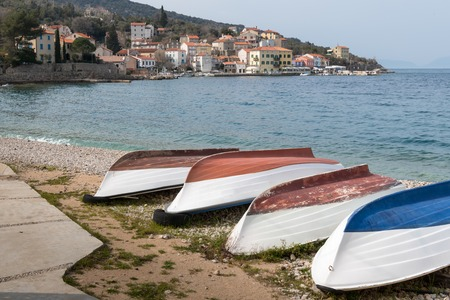 Boats lying on the beach of Valun (Island Cres, Croatia) on a cloudy day in spring