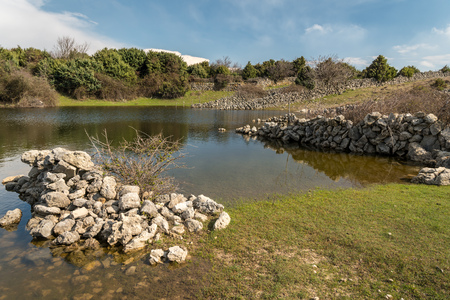 Small pond, watering place for sheep in spring near Sream (island Cres, Croatia) 스톡 콘텐츠