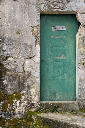Very old weathered green door made of wood, house entrance in Beli (Island Cres, Croatia)