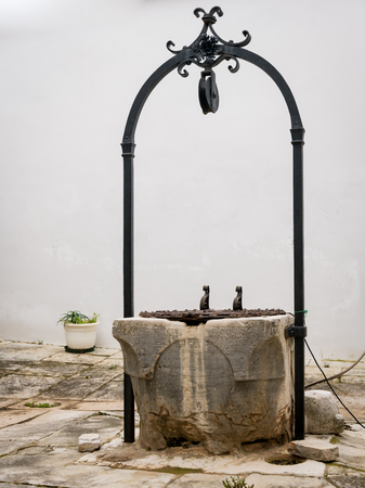 Old well, inner courtyard of church Sveti kriz in Cres (Croatia)
