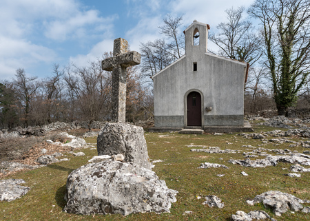 Small chapel and stone cross near Beli (island Cres, Croatia) on a cloudy day in spring
