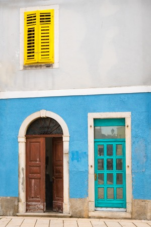 Colorful facade, blue wall, yellow shutter in the historic center of Cres, Croatia