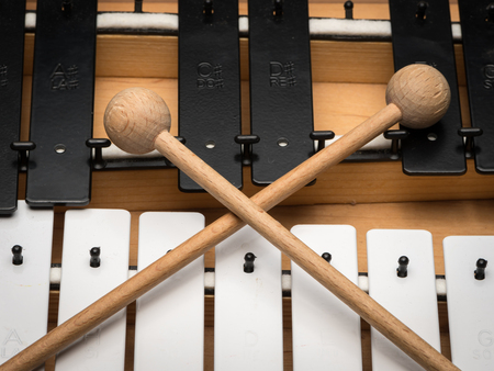 Details of a Glockenspiel with black and white keys and wooden mallets