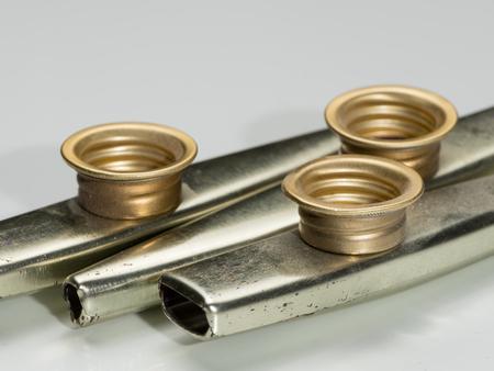 Closeup of metal kazoos on a white reflective surface