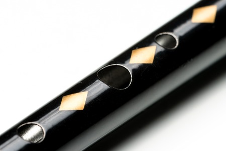 Details of a black tin whistle lying on a white reflective surface
