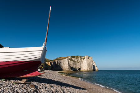 Boat in front of the halk cliffs of Etretat (Normandy France) with the natural arch Porte dAval and the stone needle called LAiguille