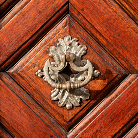 Closeup of a beautiful old doorknob made of silver on a brown door Stockfoto