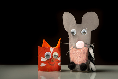 Closeup of a red cat and a grey mouse made of toilet paper roll by a child