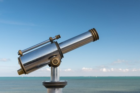 Shiny metallic telescope in front of the sea and blue sky