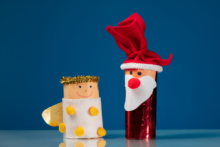 Figures of Santa Claus and an angel made of a toilet paper roll by a child on blue background Stockfoto
