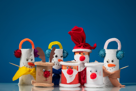 Various figures of Santa Claus, a snowmen and a reindeer made of toilet paper rolls by a child on blue background